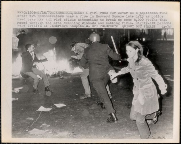 A girl runs for cover as a policeman runs after two demonstrators