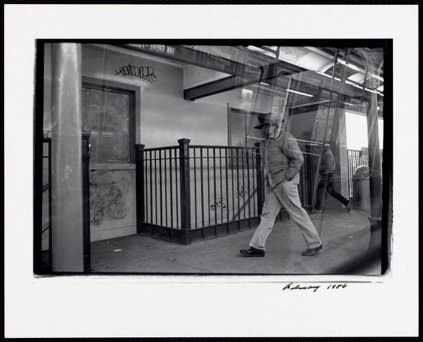 Photograph of man walking taken from inside an Orange Line train