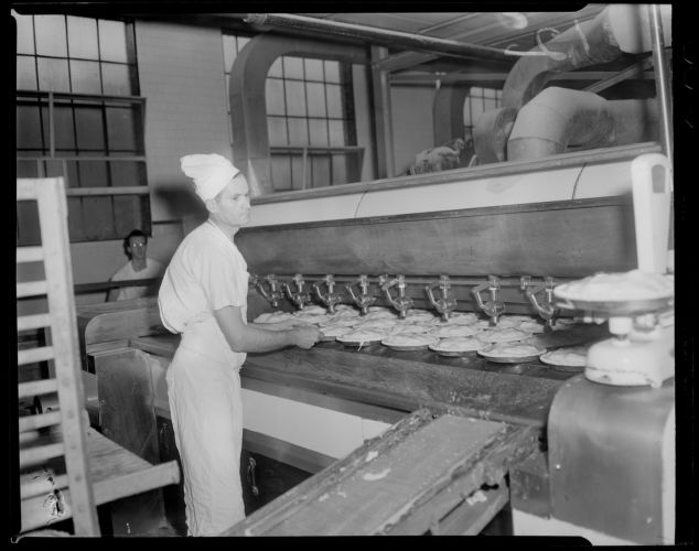 Charlie Sizilis placing pies in the oven, Table Talk factory in Worcester