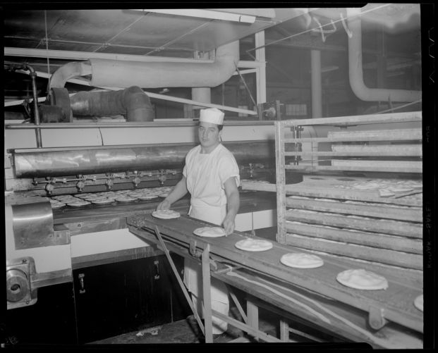 Andy Koskinas guiding pies onto conveyer belt to furnace, Table Talk factory, Worcester