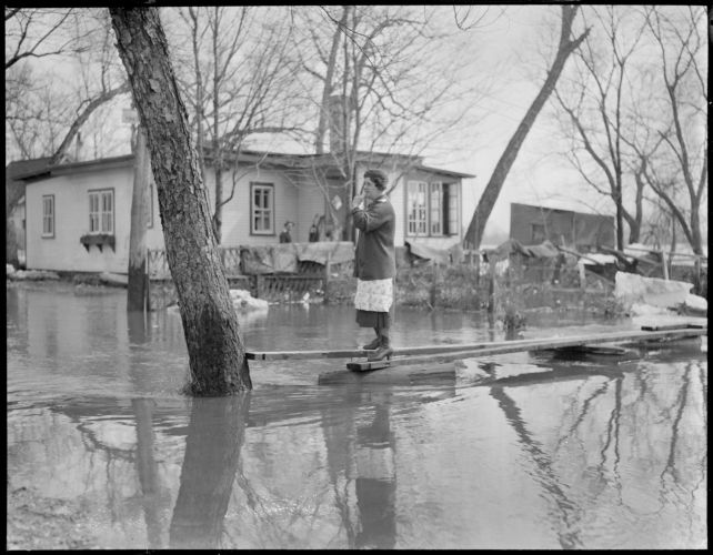 Woman walks on planks, New England flood
