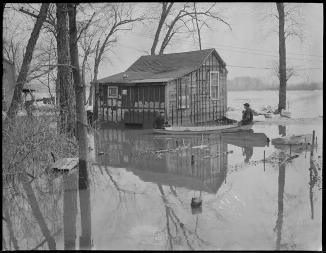 Woman and boy in boat row by cabin