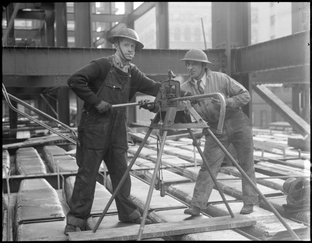 Workers building new post office wear WWI helmets to protect them from fatal rivets