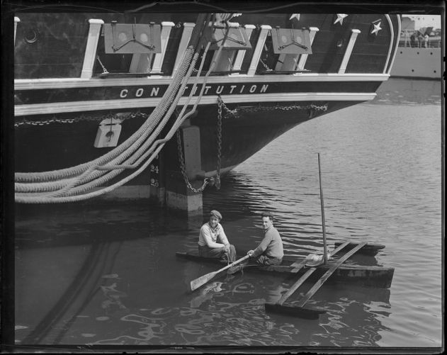 Boys in outrigger paddle under stern of the USS Constitution
