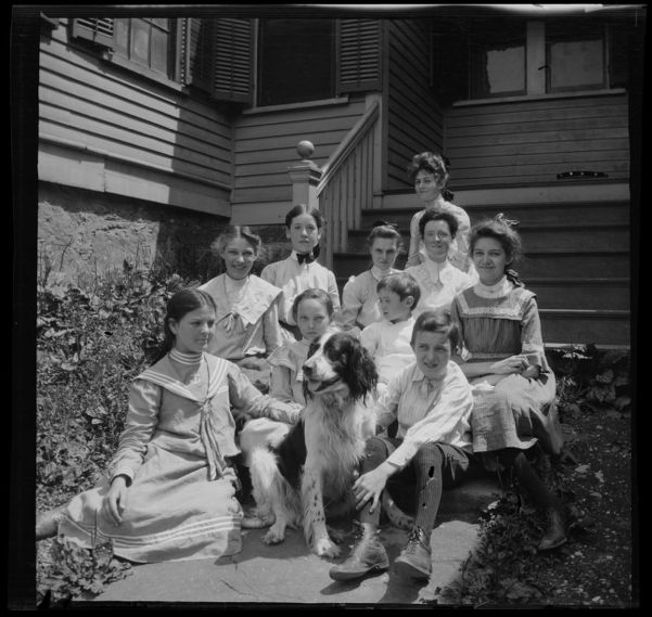 Agnes E. O'Connor, in black bow tie, and group of students on steps of South End Industrial School, Roxbury