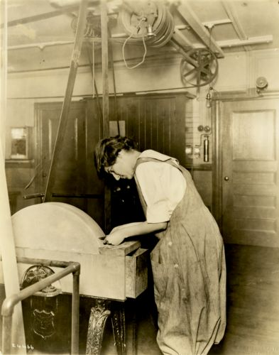 Female student using woodshop tool