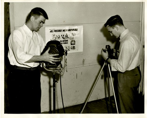 Students photographing posters for civil defense