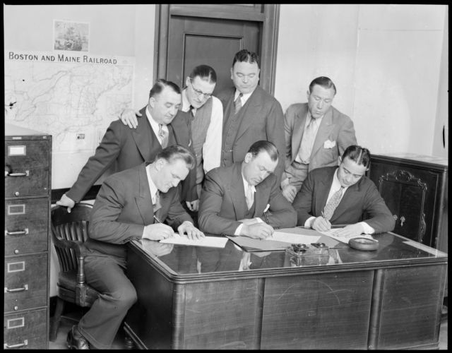 Fighters sign at Boston Garden seated L-R: Ernie Schaaf, Jack Sharkey, and Jim Maloney