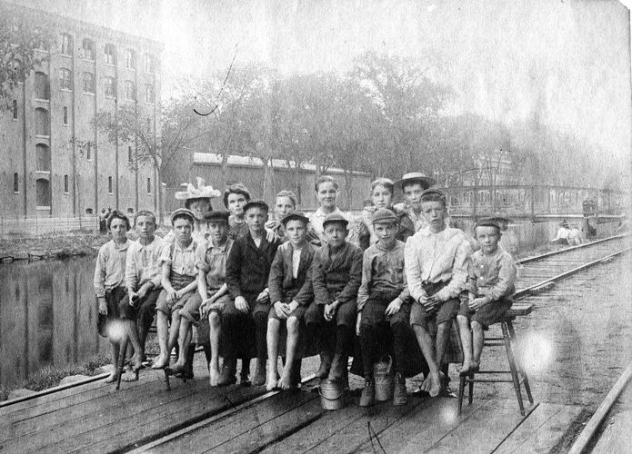 Children seated on North Canal island in front of the Pacific Mills around noon, ca.1896