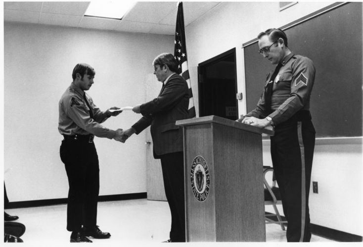 Member of Campus Police receiving document