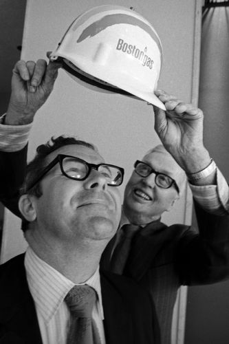 """Happy BostonGas executive gets a """"promotional"""" hard hat, downtown Boston"""