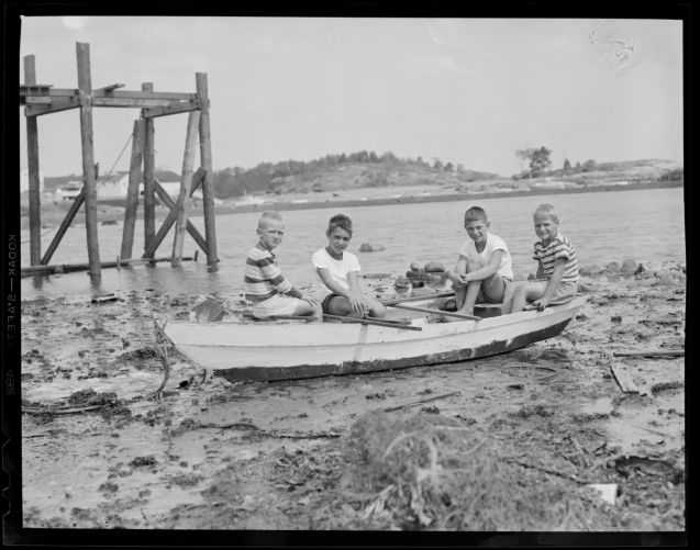 Boys sit in boat amid debris from hurricane