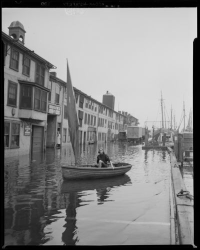 Woman in sailboat at flooded T-wharf