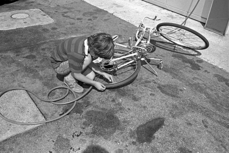Boy inflates bike tire at gas station, Gloucester