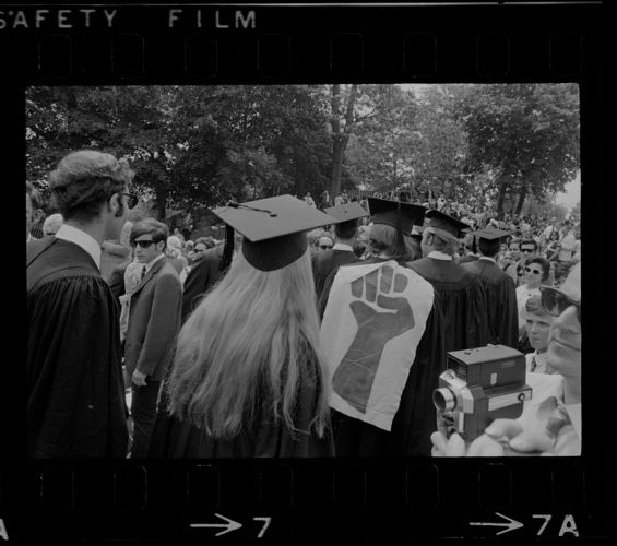 Brandeis University graduates with some wearing clenched fist, the symbol of student resistance, on the back off their robes during commencement