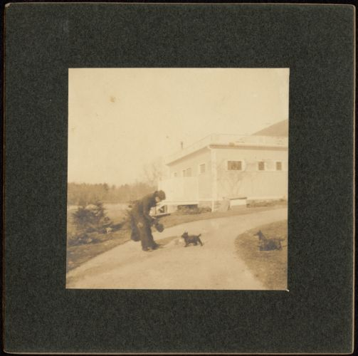 Ashdale Farm. Man with two dogs in yard near house. Print mounted on square black board.