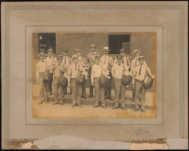 Postmen in front of Newburyport Post Office, Inn St. mailmen are wearing winter and summer hats, c. 1925