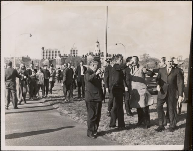 President Kennedy is shown as he made an unscheduled stop on Storrow Drive across the river from Harvard where he is shown looking over the proposed Kennedy Library sight with Harvard officials