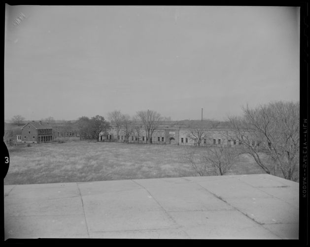 Exterior view of Fort Warren behind a row of trees with a house next to it