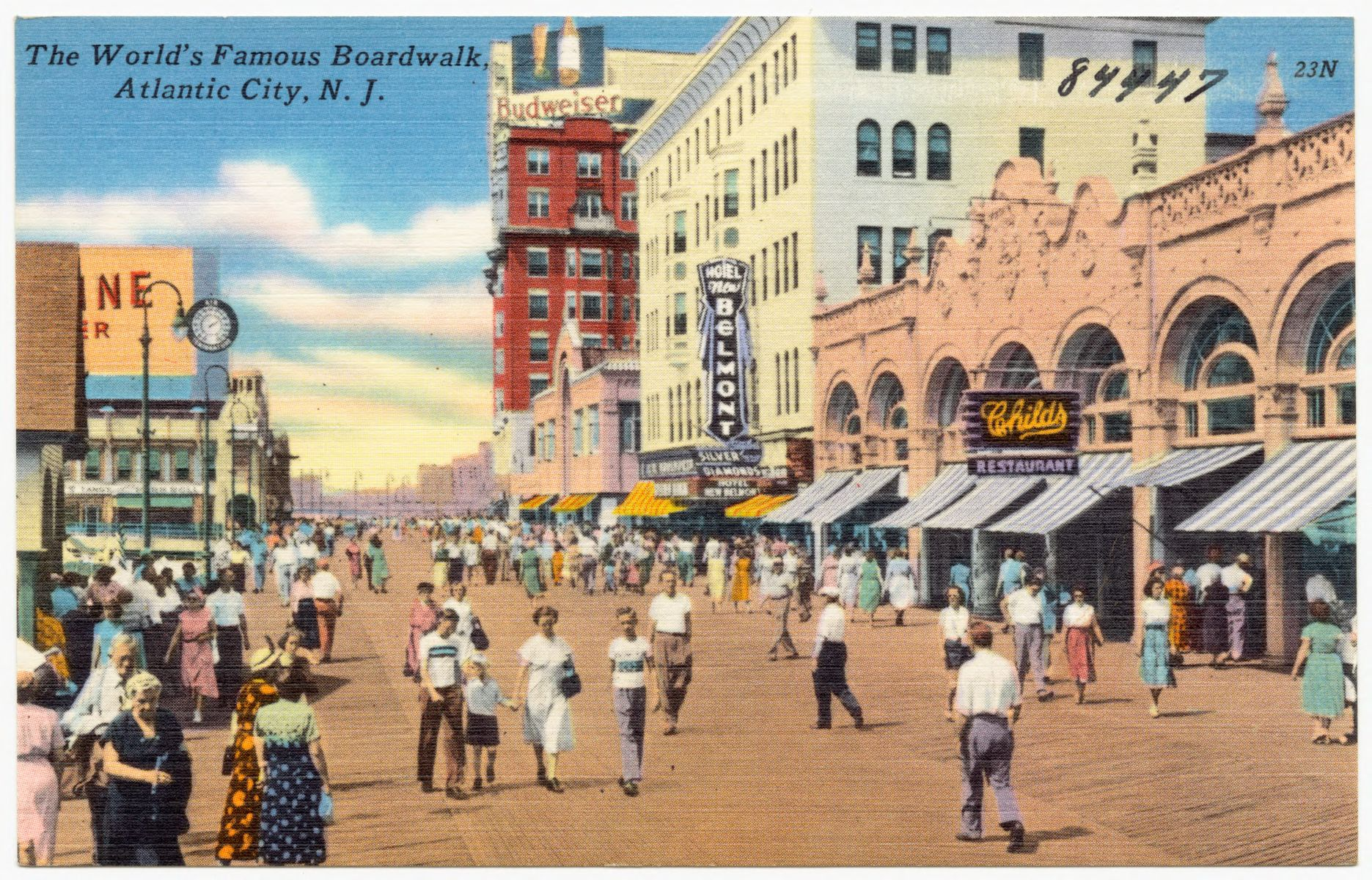 """A colorful painted postcard shows a beachside boardwalk with white families walking along it, and signs point out a movie theater, stores, and a beer advertisement. """"The World's Famous Boardwalk, Atlantic City, N.J."""" (1930) Boston Public Library, Digital Commonwealth."""